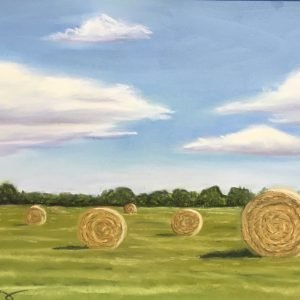 Round bales of hay sitting in green field with blue sky